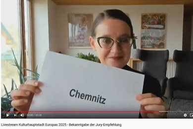 And the winner is ... Jury-Vorsitzende Sylvia Amann hält im Livestream den Namen der Gewinnerstadt in die Kamera: Chemnitz!